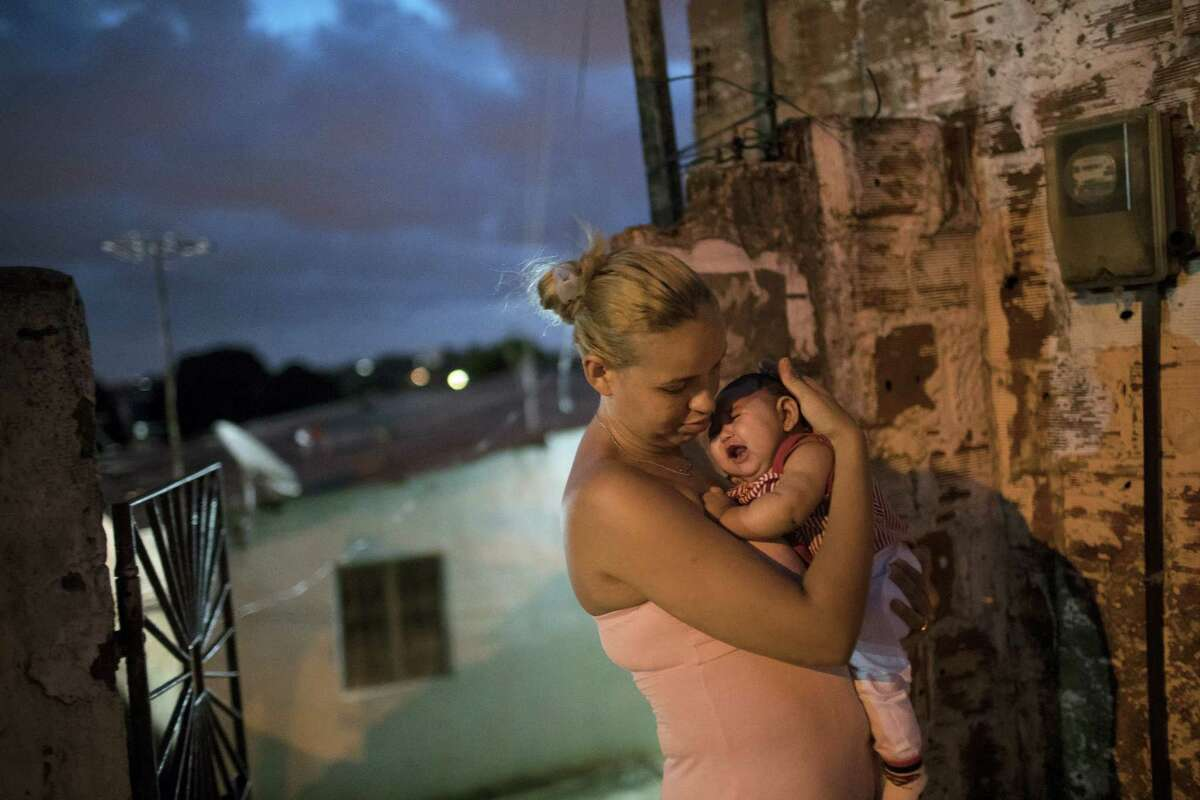 Gleyse Kelly da Silva, 27, holds her daughter Maria Giovanna, who was born with microcephaly, outside their house in Recife, Pernambuco state, Brazil on Jan. 27, 2016. Brazilian officials still say they believe there's a sharp increase in cases of microcephaly and strongly suspect the Zika virus, which first appeared in the country last year, is to blame.