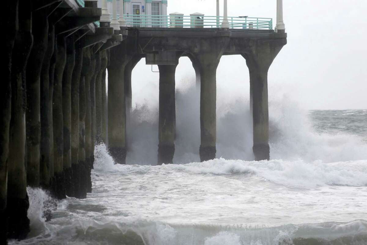 The Manhattan Beach pier is hit by high waves caused by the El Nino storm in Manhattan Beach, Calif. on Jan. 6, 2016. The system Wednesday will pack colder temperatures, stronger winds and heavier rainfall than the two previous storms that have battered the state since the weekend.