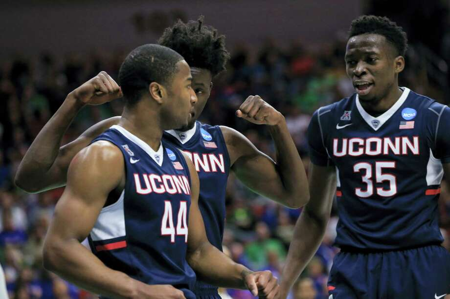 Connecticut's Rodney Purvis (44), Amida Brimah (35) and Daniel Hamilton, center, celebrate after a foul called against Colorado, during a first-round men's college basketball game in the NCAA Tournament in Des Moines, Iowa, Thursday, March 17, 2016. Connecticut won 74-67.(AP Photo/Nati Harnik) Photo: AP / Copyright 2016 The Associated Press. All rights reserved. This material may not be published, broadcast, rewritten or redistributed without permission.