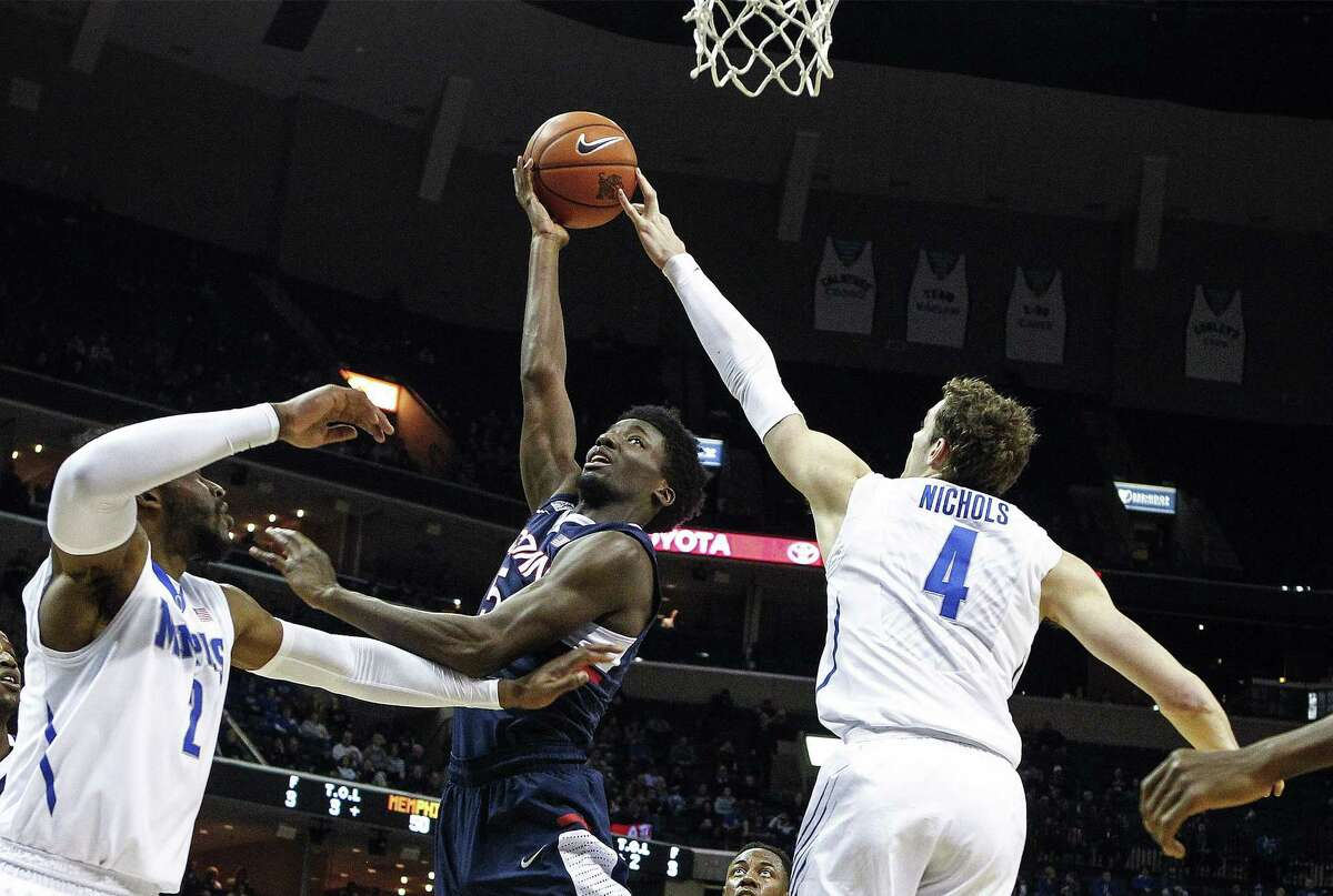 Memphisí Austin Nichols, right, blocks the shot of Connecticutís Daniel Hamilton as Memphis' Shaq Goodwin helps defend during the second half of an NCAA college basketball game Thursday, Feb. 19, 2015, in Memphis, Tenn. (AP Photo/The Commercial Appeal, Mark Weber)