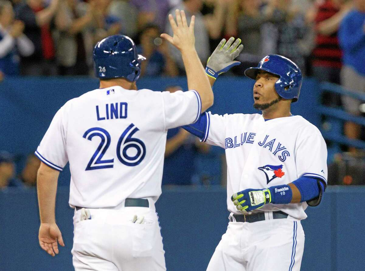 The Blue Jays' Edwin Encarnacion, right, is congratulated by teammate Adam Lind after he hit a two-run home run on Thursday in Toronto.
