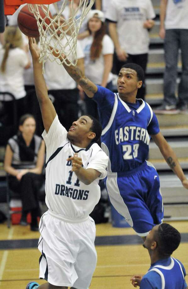 Middletown sophomore point guard Makai Hunter elevates for two as Bristol Eastern's Daron McKoy defends Friday night at LaBella-Sullivan Gymnasium at MHS. The Blue Dragons defeated Bristol Eastern, 60-41. Photo: Catherine Avalone — The Middletown Press  / TheMiddletownPress