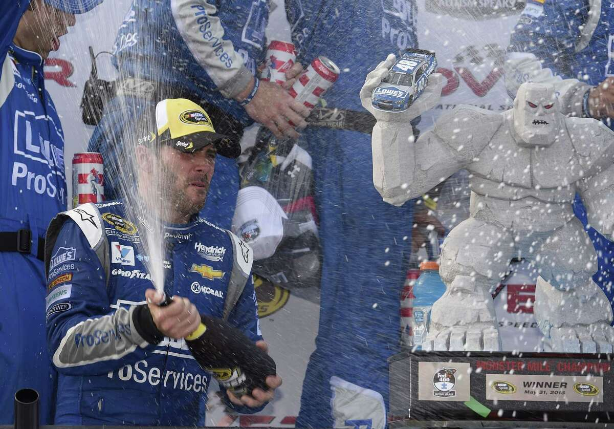 Jimmie Johnson sprays champagne as he celebrates in Victory Lane after he won at Dover International Speedway on Sunday.