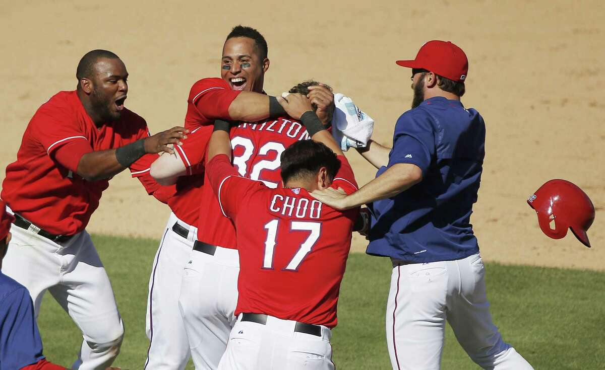 The Rangers' Josh Hamilton (32) is mobbed by teammates after his two-run walkoff double during the ninth inning on Sunday.