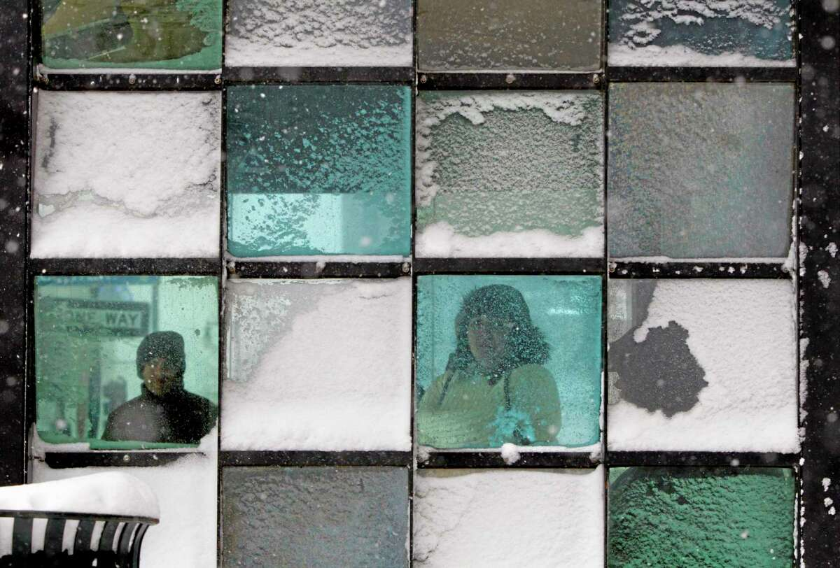 In this Feb. 8, 2013 file photo, riders wait in a bus stop where color-tinted windows collect snow during a storm in Portland, Maine. Less than 70 percent of 19-year-olds now have a drivers licence, down from 87 percent two decades ago, government figures show. (AP Photo/Robert F. Bukaty, File)