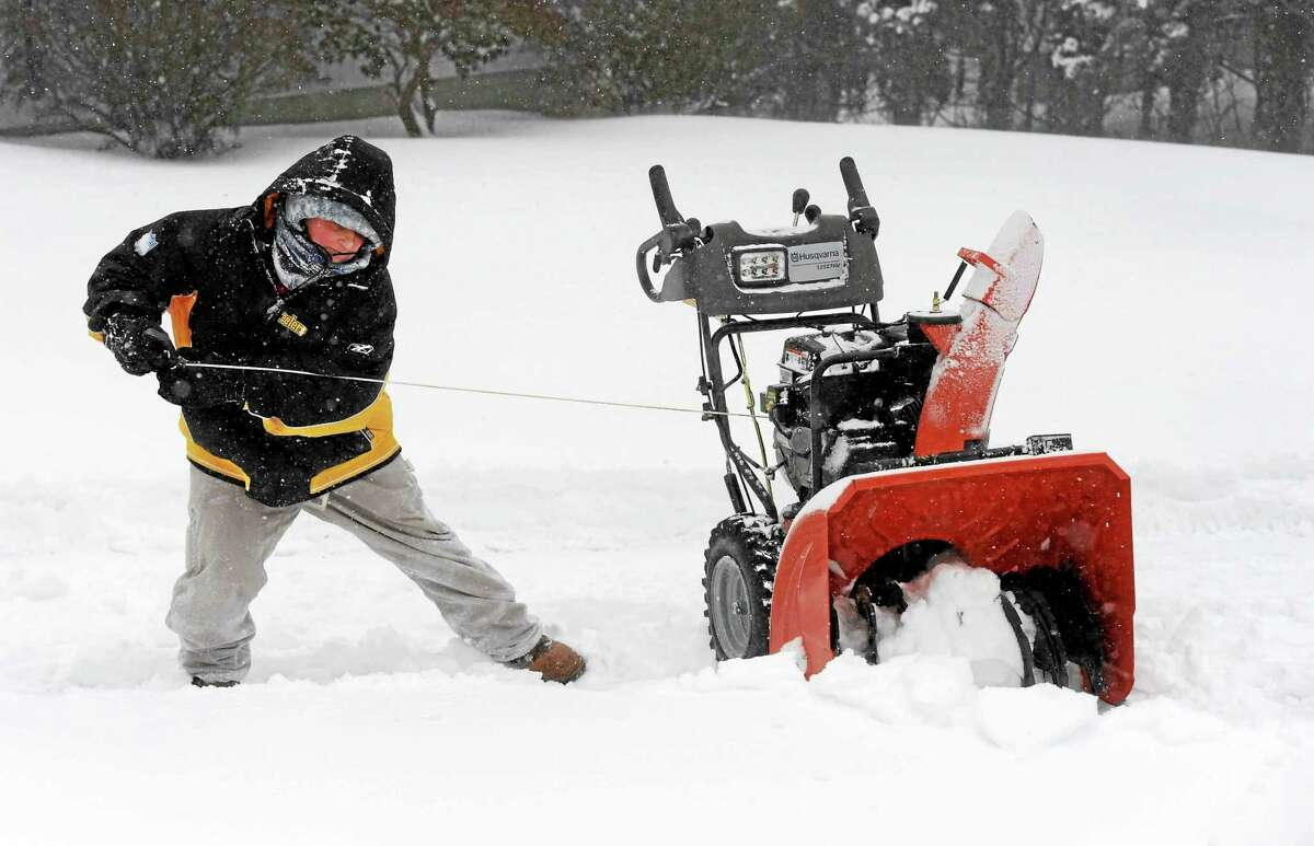 Jen Hanrahan pulls hard to start her snowblower before clearing her driveway on Pine Orchard Road in Branford on Tuesday.