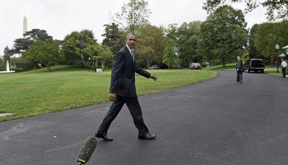 President Barack Obama walks past members of the press corp after returning to the White House in Washington on Tuesday after spending three days in New York and the United Nations. Photo: AP Photo  / AP