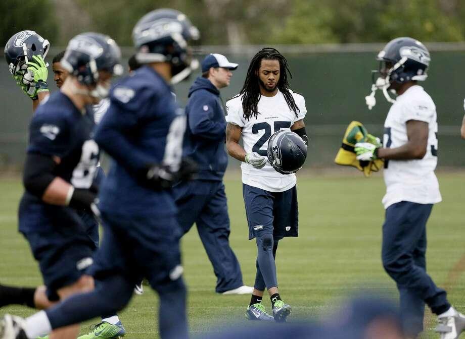 Seattle Seahawks cornerback Richard Sherman puts his helmet on during practice Thursday in Tempe, Ariz. Photo: Matt York — The Associated Press  / AP