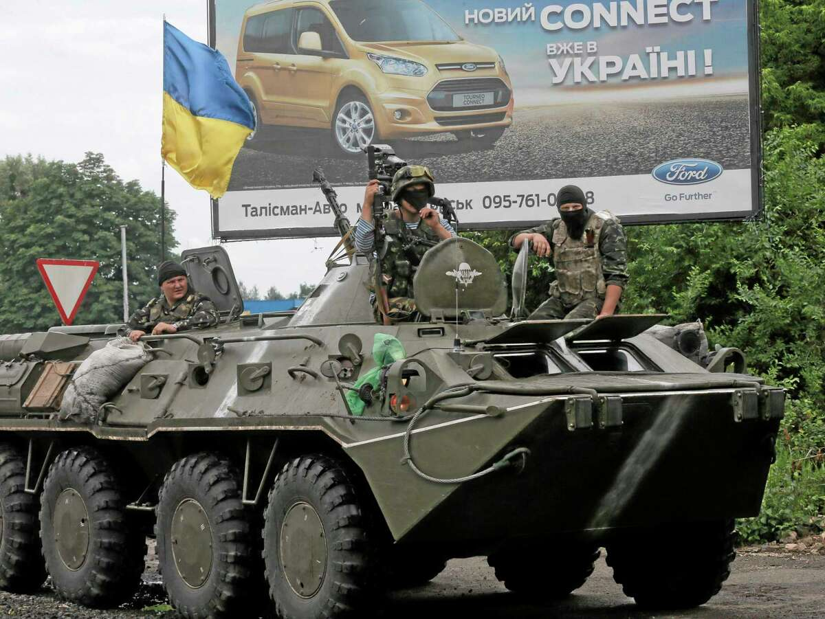 A Ukrainian army APC takes position during a battle with pro-Russian separatist fighters at Slovyansk, Ukraine, Saturday, May 31, 2014. The Ukrainian government army forces have established a ring of checkpoints around Slovyansk, the epicenter of the Ukrainian conflict. (AP Photo/Efrem Lukatsky)