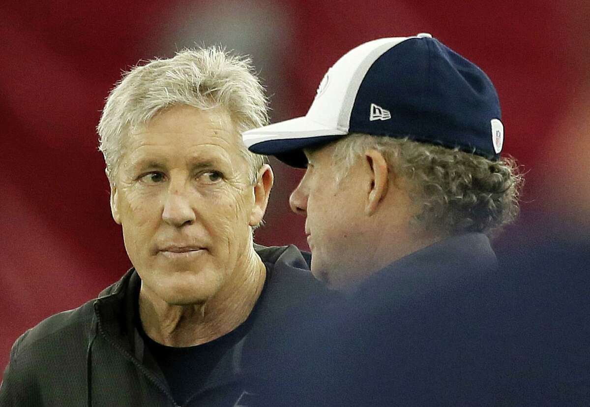 Seattle Seahawks head coach Pete Carroll, left, talks with quarterbacks coach Carl Smith during Friday's practice in Tempe, Ariz.