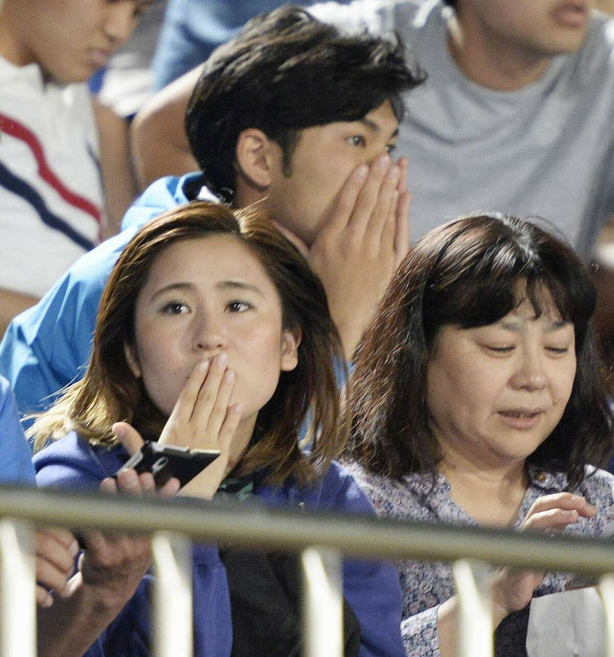 Japanese soccer fans react to a strong earthquake as they watch a J-League soccer match between the Shonan Bellmare and the Sanfrecce Hiroshima at BMW Stadium in Hiratsuka, southwest of Tokyo Saturday, May 30, 2015. A powerful and extremely deep earthquake struck a group of remote Japanese islands and shook Tokyo on Saturday, but officials said there was no danger of a tsunami, and no injuries or damage were immediately reported. (Munehide Someya/Kyodo News via AP)
