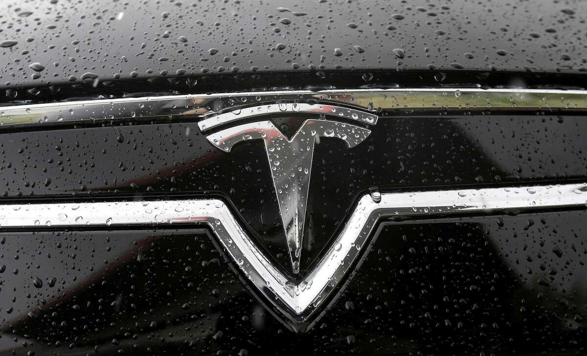 A Tesla symbol is shown on a car outside of the Tesla factory in Fremont, Calif., Thursday, May 14, 2015. (AP Photo/Jeff Chiu)