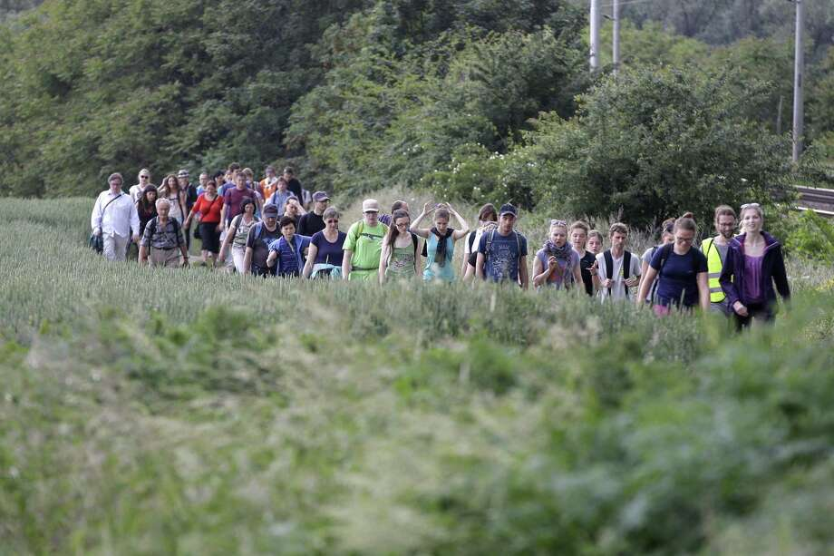 Participants take part in a 20-mile walk between the town of Pohorelice and the city of Brno, Czech Republic, Saturday, May 30, 2015. In a rare gesture of reconciliation, hundreds took part in a walk on Saturday to commemorate some 1,700 ethnic Germans who died 70 years ago during their expulsion from the second largest Czech city of Brno. On May 30, 1945, city authorities of the then liberated Brno herded more than 20,000 local ethnic Germans, including children, women and elderly, to escort them on foot out of the country in what is now known as the Brno death march. (AP Photo/Petr David Josek) Photo: AP / AP