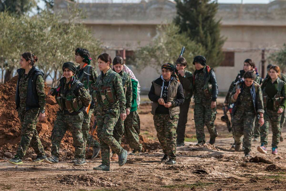 In this photo released on May 16, 2015, provided by the Kurdish fighters of the People's Protection Units (YPG), which has been authenticated based on its contents and other AP reporting, Kurdish female fighters of the YPG, carry their weapons as they walk in the frontline of Kery Sabee village, northeast Syria. In contrast to the failures of the Iraqi army, in Syria Kurdish fighters are on the march against the Islamic State group, capturing towns and villages in an oil-rich swath of the country's northeast in recent days, under the cover of U.S.-led airstrikes. (The Kurdish fighters of the People's Protection Units via AP)