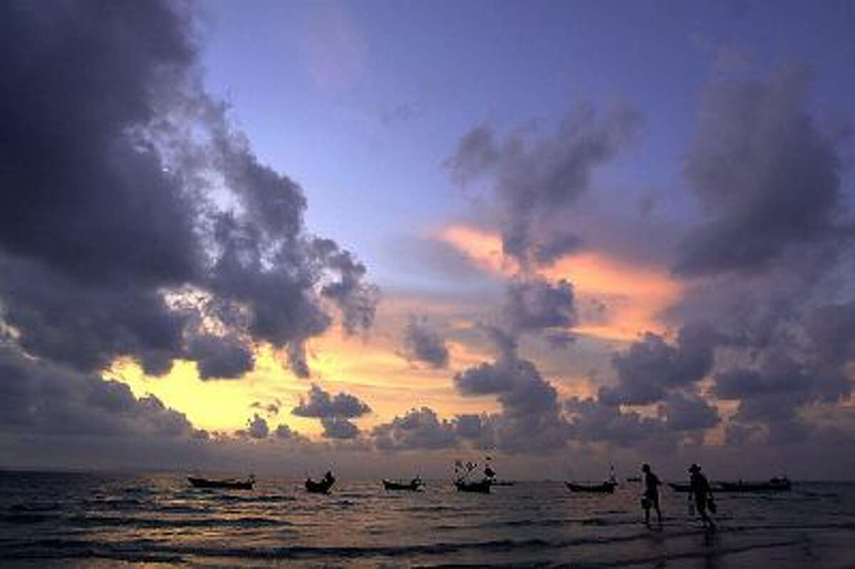 Two Cambodian fishermen go for night fishing as the sun goes down in the seaside resort of Sihanoukville some 230kms South of Phnom Penh, 22 April 2001.