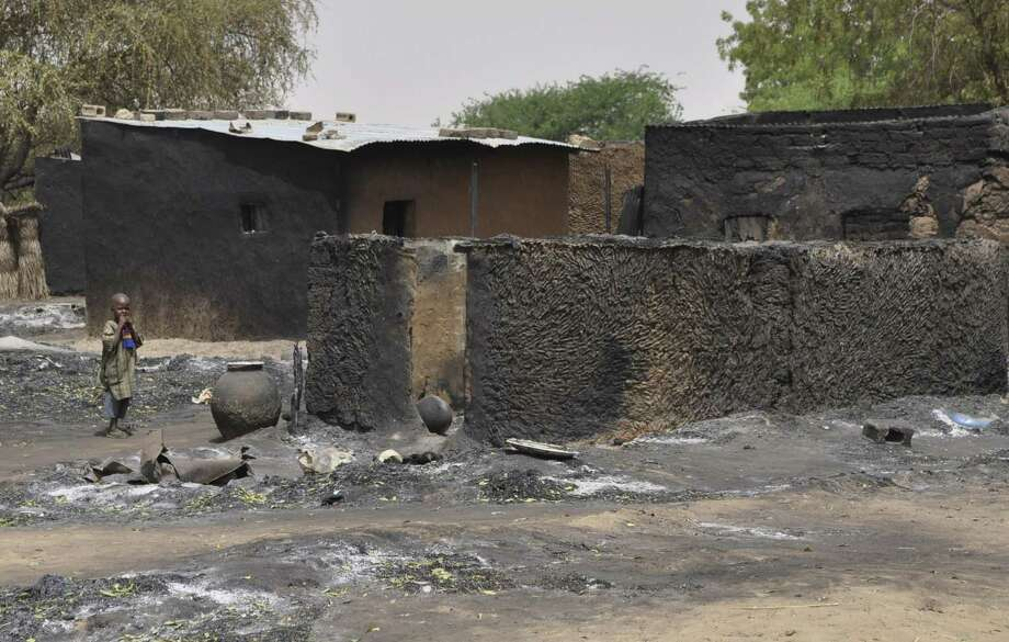 "A child walks past burnt out houses following Sunday's attack by Boko Haram militants in Gubio, Nigeria, Tuesday, May 26, 2015. Children are now being seen as potential threats after an ""alarming spike"" in suicide bombings by girls and women being used by Boko Haram militants in northeastern Nigeria, the U.N. children's agency said Tuesday. (AP Photo/Jossy Ola) Photo: AP / AP"