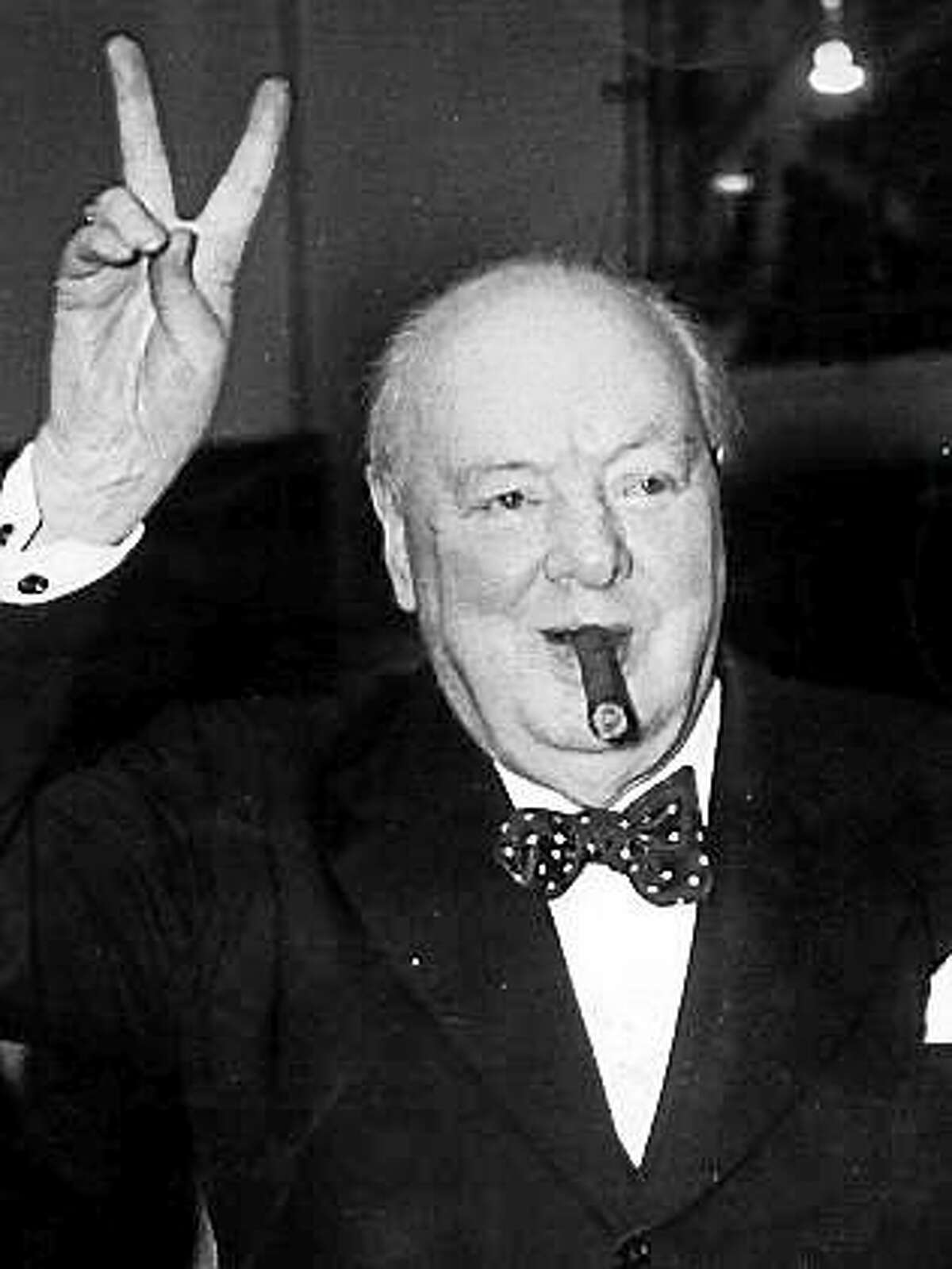 Winston Churchill flashing his famour victory sign and smoking his iconic cigar.