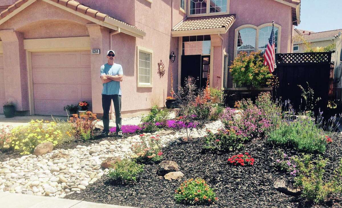 Rick Jenkins poses for a photo in the front yard of the Jenkins home in Gilroy, Calif. Jenkins took advantage of a rebate program last year and replaced his lawn with a dry, rocky river bed.