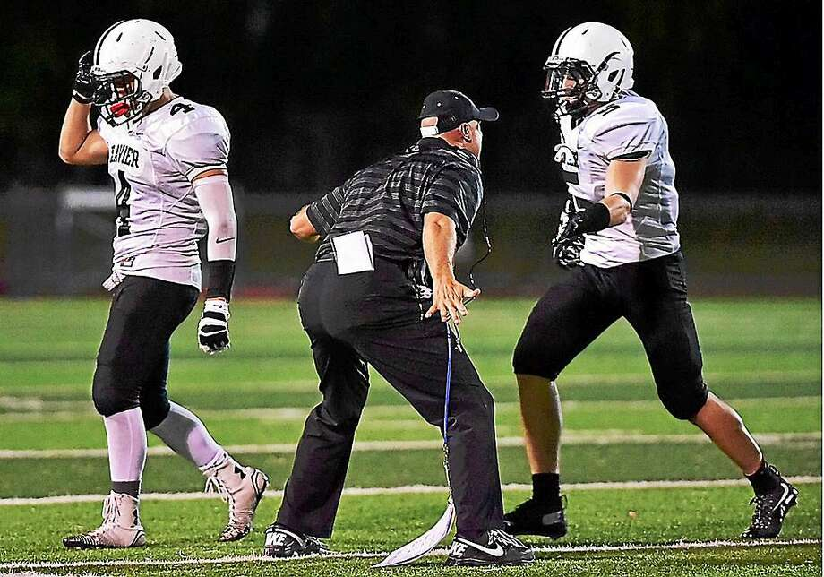 Xavier linebackers Anthony Caramanica (left) and Spencer McManus (far right) come off the field after a defensive stop earlier this year. Photo: Catherine Avalone -- The Middletown Press
