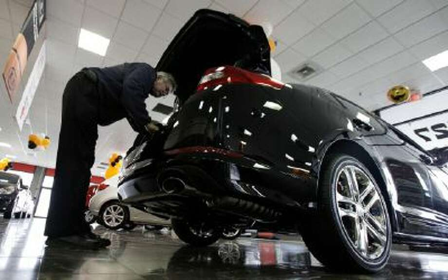 A shopper checks a Kia Optima inside a Kia car dealership in Elmhurst, Ill.