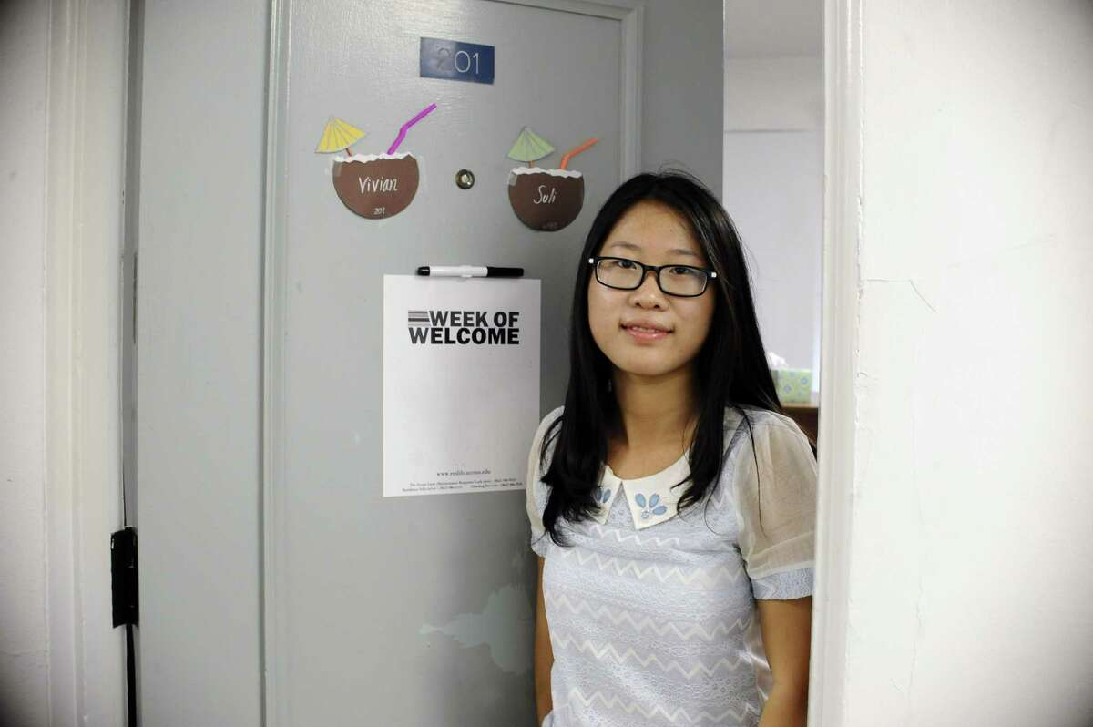 In this Friday, Sept.18, 2015 photo, University of Connecticut sophomore, Anyi Yang of Beijing, poses for a photograph next to her American name Vivian on the door of her dorm, in Storrs, Conn. A surge of students from China is leading U.S. universities to confront the challenges of integrating them more into American campus life.