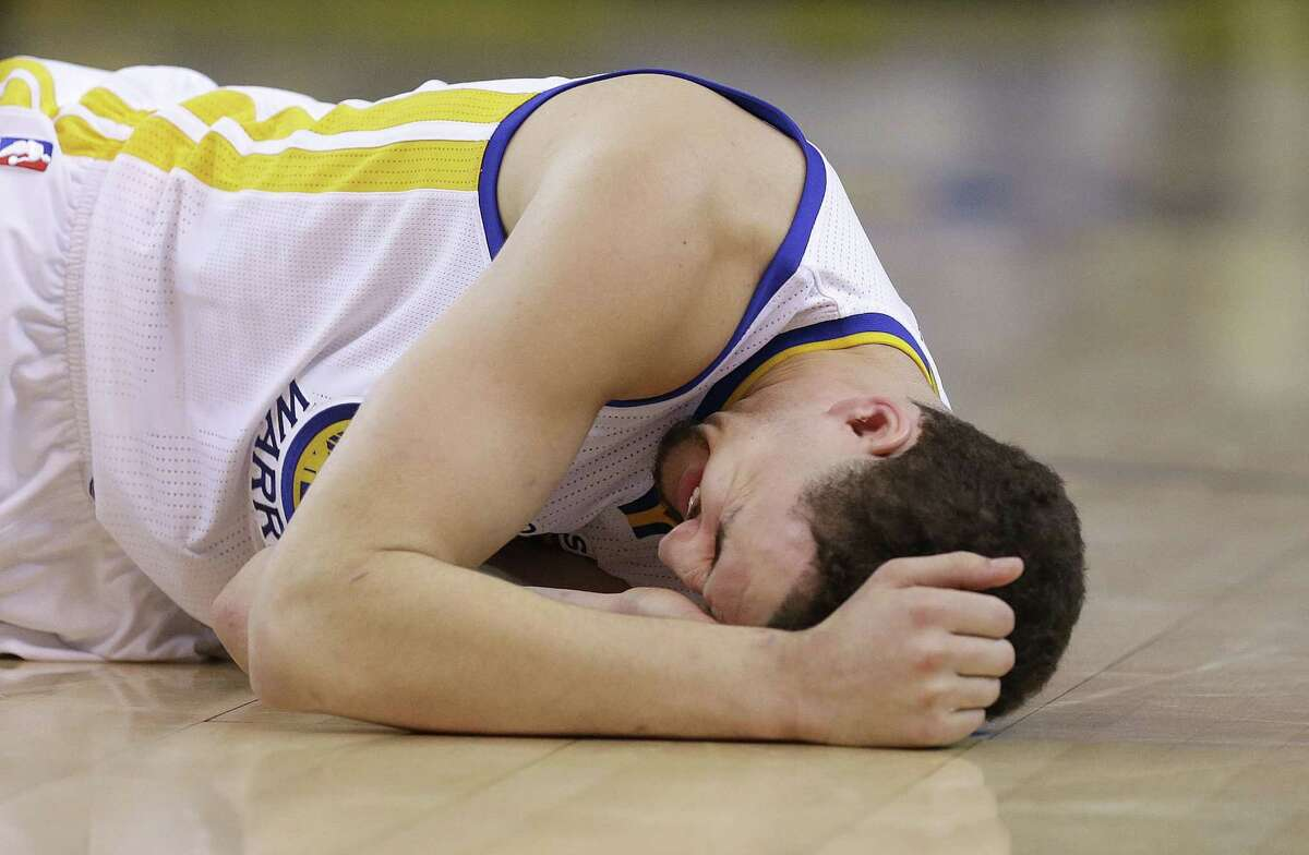 Golden State Warriors guard Klay Thompson reacts Wednesday after taking a knee to his head from Houston Rockets forward Trevor Ariza.