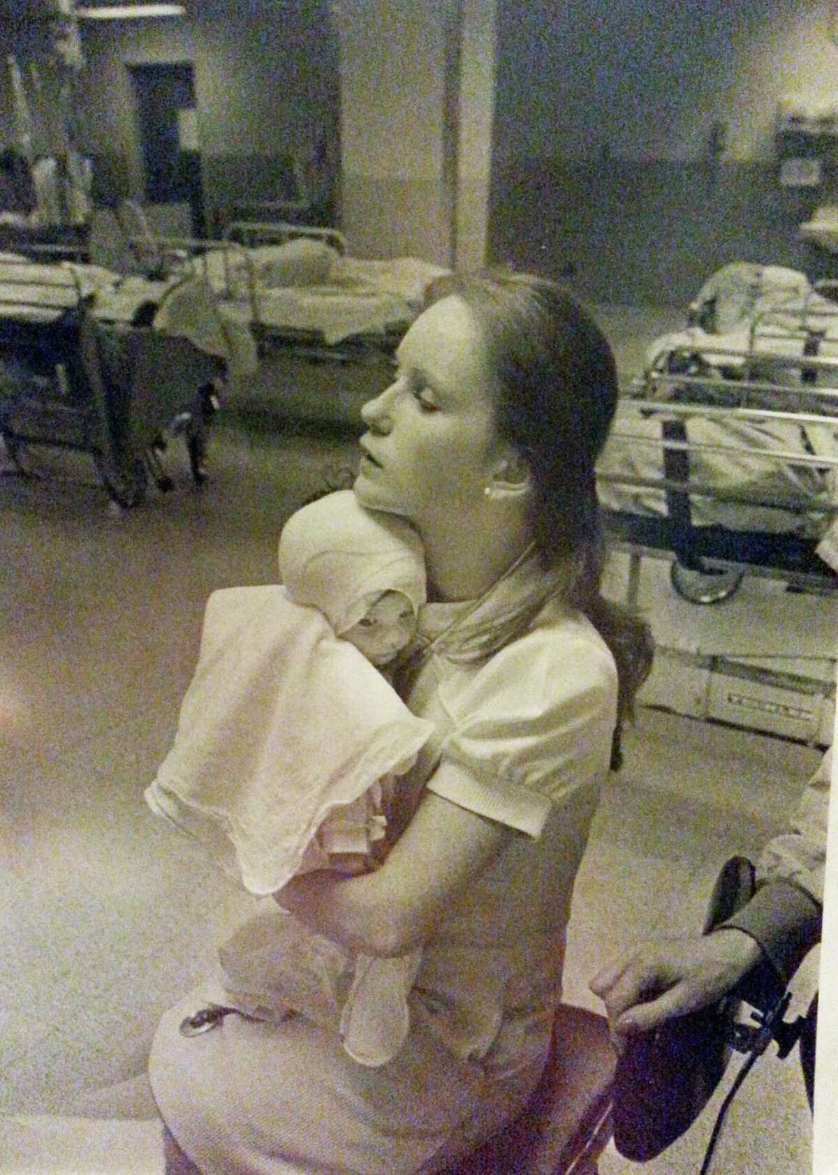 In this 1977 photo provided by Albany Medical Center, nurse Susan Berger cuddles infant Amanda Scarpinati, who had been severely burned by a steam vaporizer at home, in the pediatric unit at Albany Medical Center in Albany N.Y. Scarpinati kept the hospitalís annual report that published the photo and was comforted by the picture when she was bullied for her burn scars as a child. She recently used social media to learn Bergerís identity so she could thank her for her loving care. Albany Medical Center has arranged for the two women to meet on Tuesday, Sept. 29, 2015.
