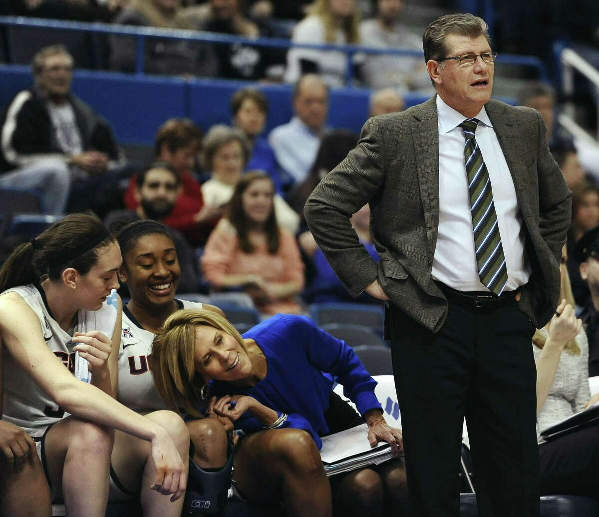 UConn associate head coach Chris Dailey, center, leans over to see the play around head coach Geno Auriemma, right, as players Breanna Stewart, left, and Morgan Tuck look on during the second half Wednesday.