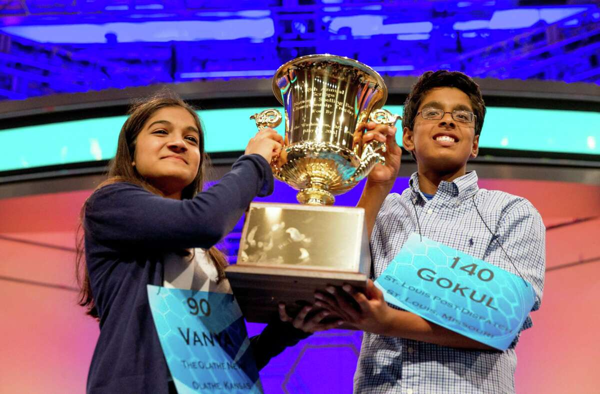 Vanya Shivashankar, left, 13, of Olathe, Kan., and Gokul Venkatachalam, 14, of St. Louis, hold up the championship trophy as co-champions after winning the finals of the Scripps National Spelling Bee, Thursday, May 28, 2015, in Oxon Hill, Md. (AP Photo/Andrew Harnik)