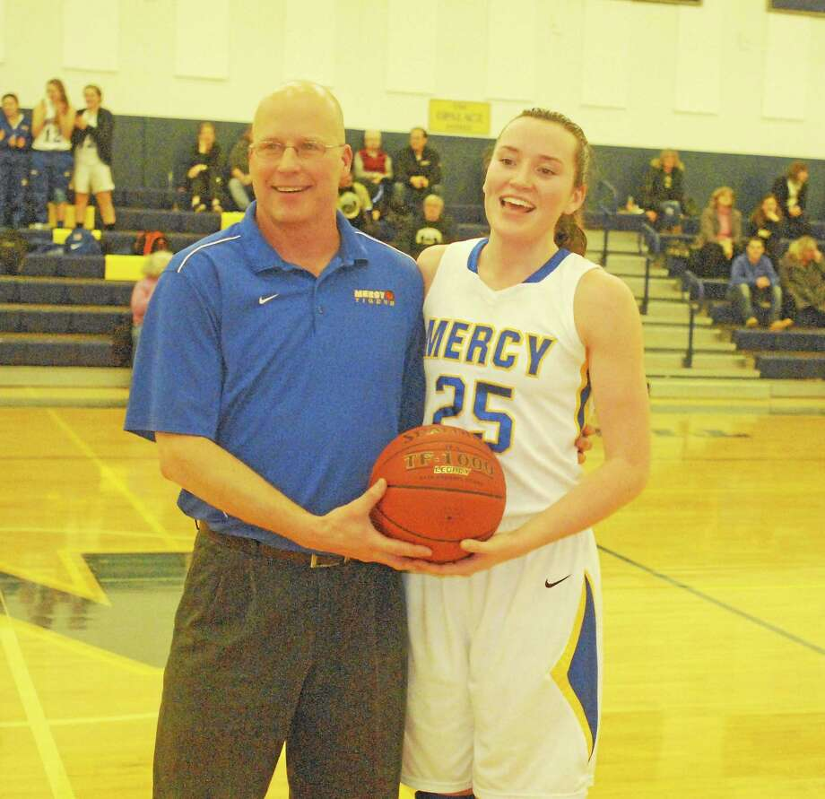 Mercy senior Maura Fitzpatrick, pictured with Tigers coach Tim Kohs, scored her 1,000th career point Thursday night in Mercy's victory over Law. Photo: Jimmy Zanor — Middletown Press