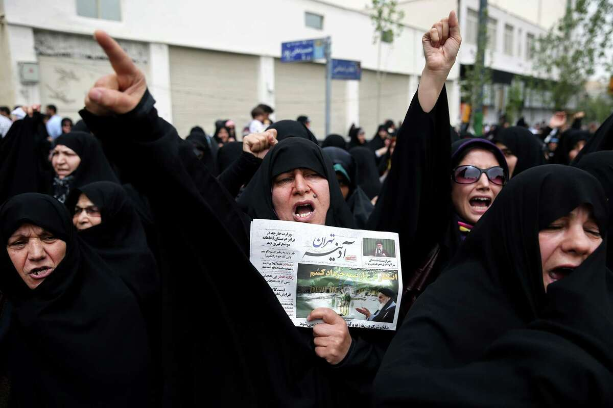 A group of Iranian worshippers chant slogans in a demonstration over negotiations with world powers on Iran's nuclear program, after their Friday prayer, in Tehran, Iran, Friday, May 29, 2015. U.S. Secretary of State John Kerry will meet with Iranian Foreign Minister Mohammad Javad Zarif in Geneva on Saturday in an effort to move the nuclear talks forward ahead of a June 30 target date for a deal. Newspaper shows an image and quote from the late Iranian revolutionary founder Ayatollah Khomeini. (AP Photo/Ebrahim Noroozi)