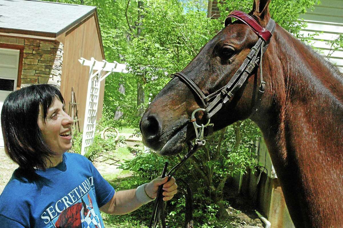 Marilyn Davis, of East Haddam, is pictured here with Lacey, one of her horses. She recently published Maddie and Beanie's Magical Journey.