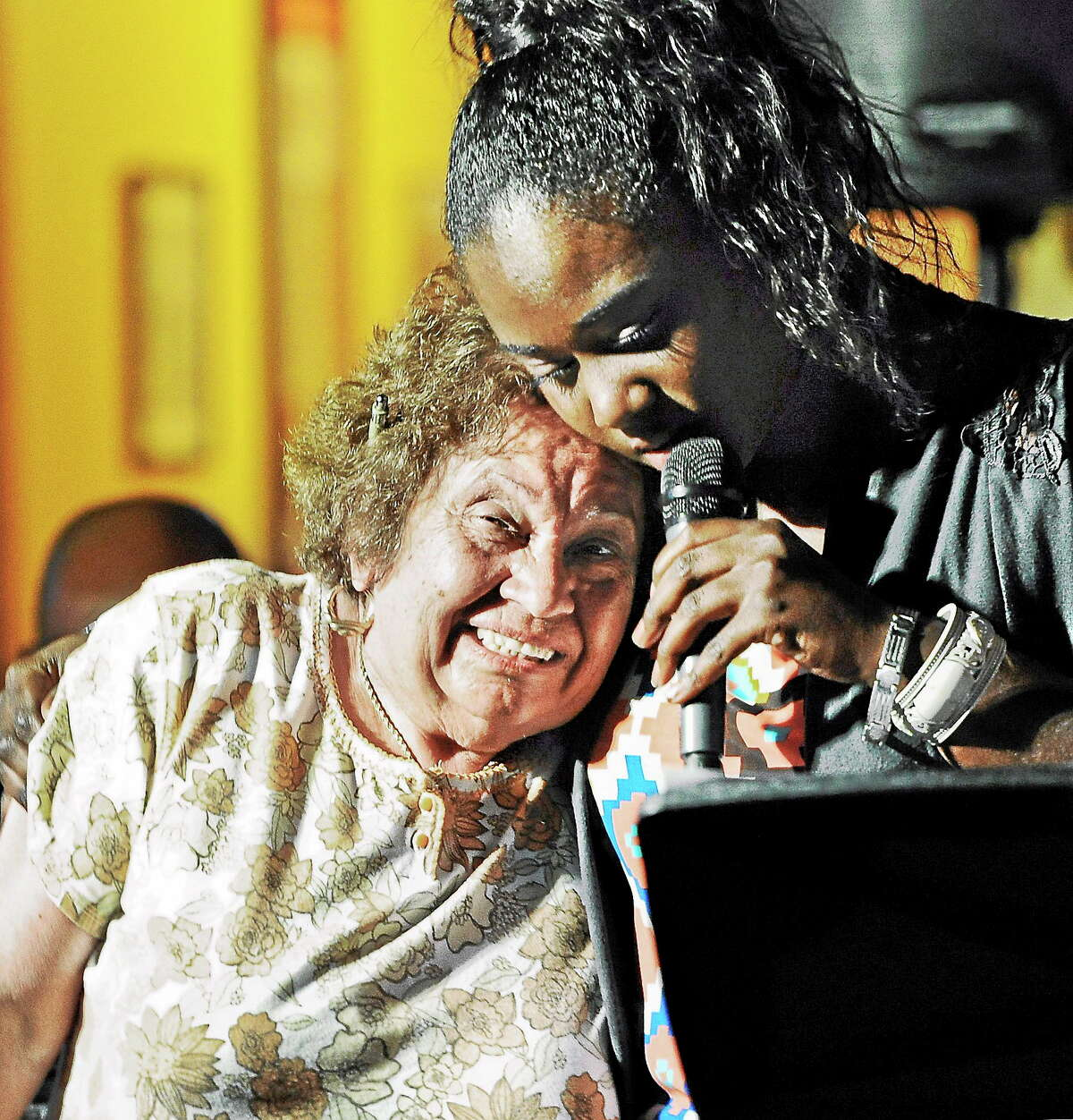 Nekita Waller performs to a smiling fan during a show at Red Rock Tavern in Hartford last summer. The Middletown vocalist is planning to travel around town next week in singing love-themed songs to area businesses and homes for Valentine's Day.
