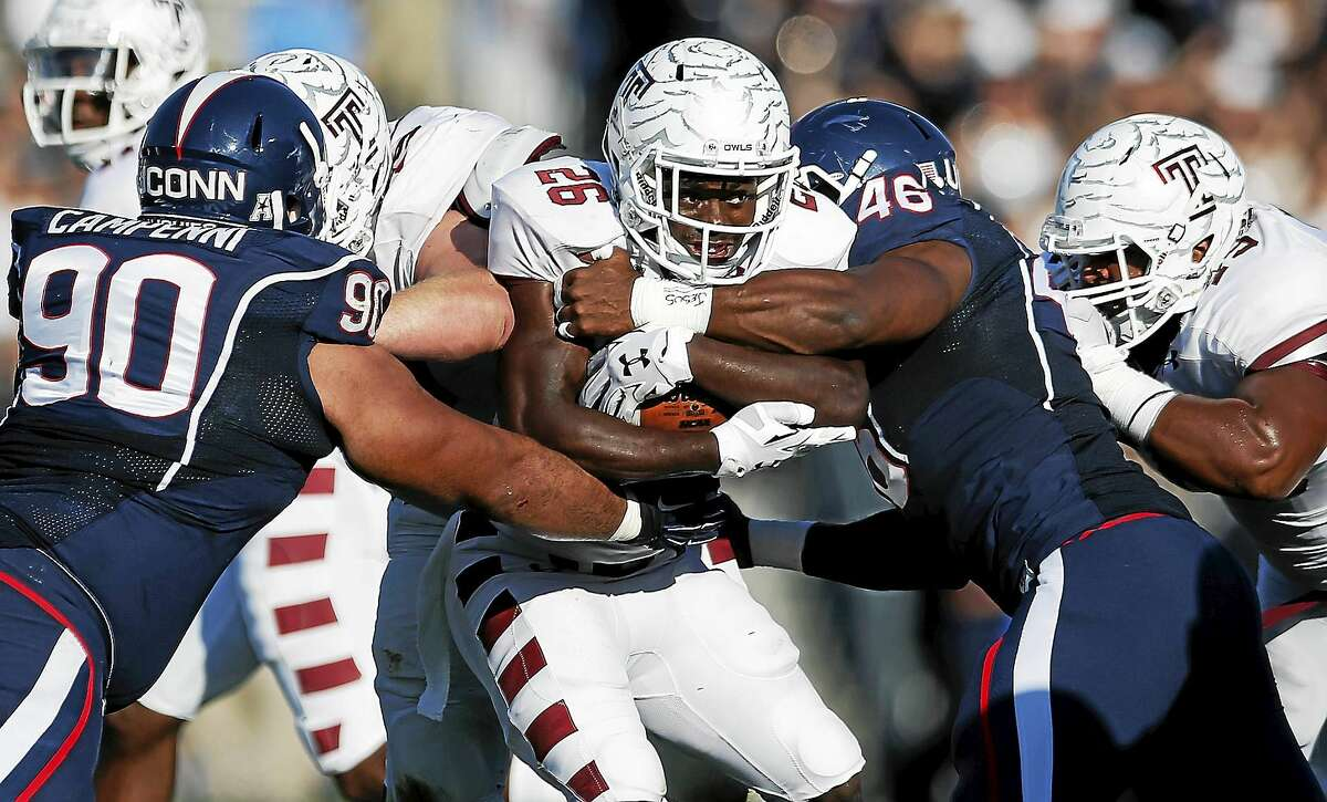 Connecticut defensive tackle Julian Campenni (90) and linebacker Marquise Vann (46) tackle Temple running back Jamie Gilmore (26) during the first quarter of an NCAA college football game in East Hartford, Conn., Saturday, Sept. 27, 2014. (AP Photo/Michael Dwyer)