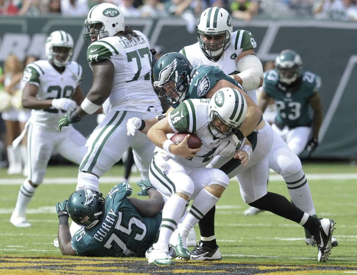 Jets quarterback Ryan Fitzpatrick (14) is sacked during Sunday's loss to the Eagles.