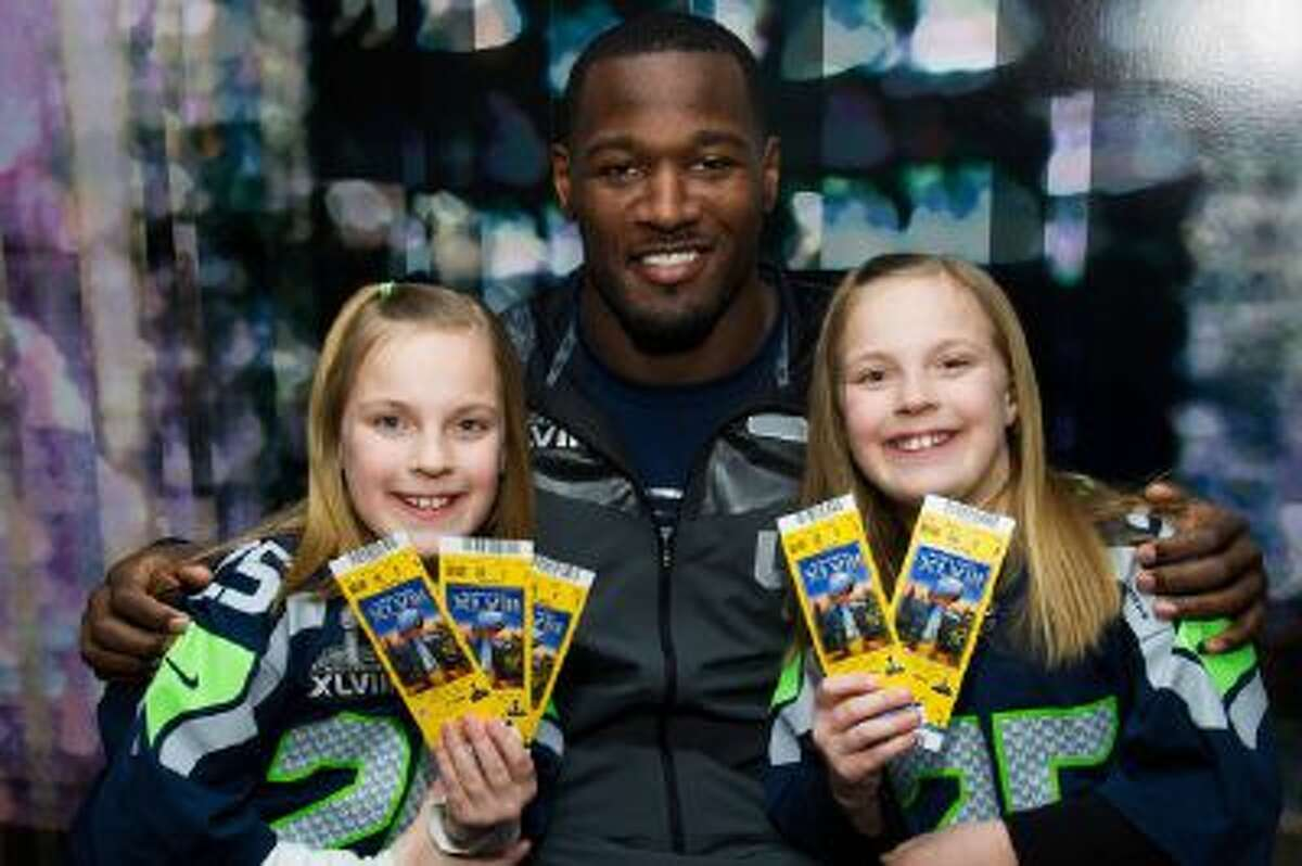 On behalf of Duracell, Derrick Coleman of the Seattle Seahawks, center, presented surprise tickets to Super Bowl XLVIII to Erin Kovalcik, left, and Riley Kovalcik, right, and their family, on Tuesday, Jan. 28, 2014 in Hoboken, N.J.