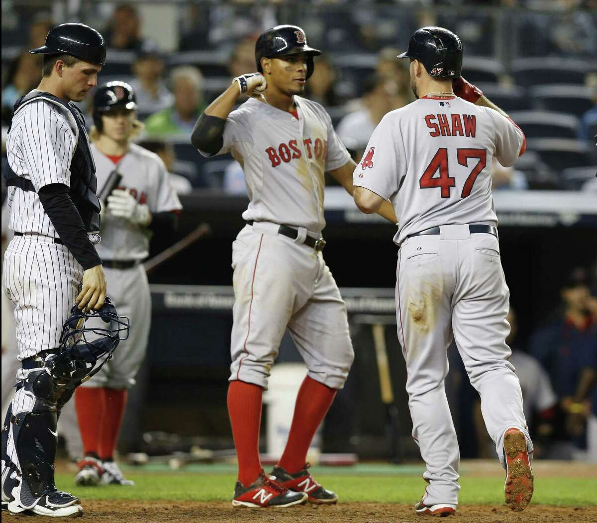 Yankees catcher John Ryan Murphy reacts as Xander Bogaerts, center, greets Red Sox's Travis Shaw (47) after scoring on Shaw's sixth-inning, two-run home run.