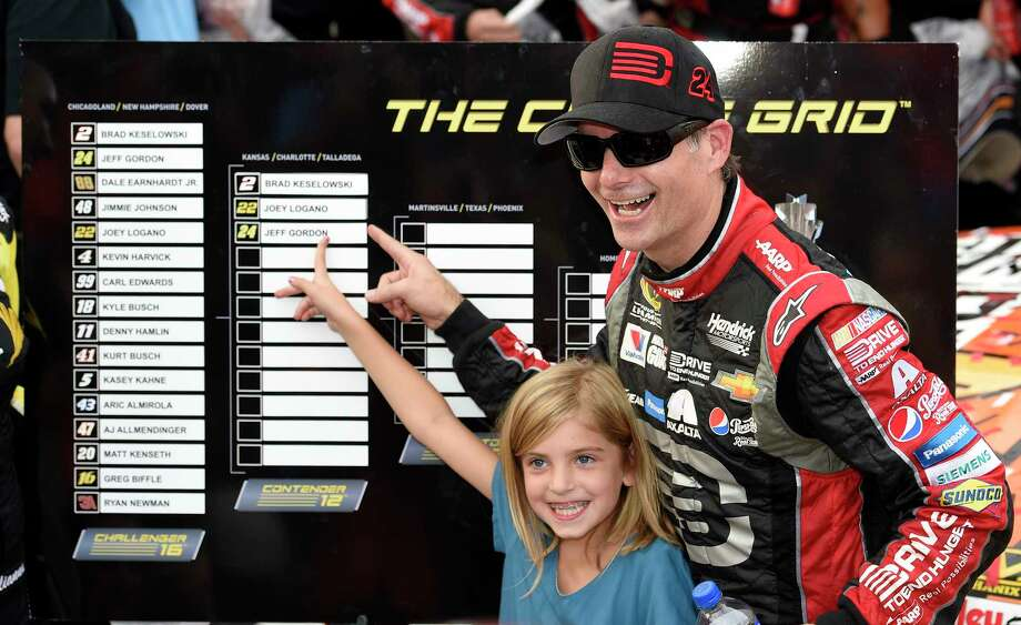 Jeff Gordon, right, and his daughter Ella Sofia, left, point to his name on the Chase Grid in Victory Lane after he won at Dover International Speedway on Sunday. Photo: Nick Wass — The Associated Press  / FR67404 AP