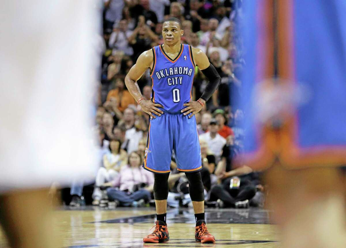 Oklahoma City's Russell Westbrook watches as teammate Kevin Durant shoots a free throw during the second half of Game 5 of the Western Conference finals against the Spurs on Thursday in San Antonio.