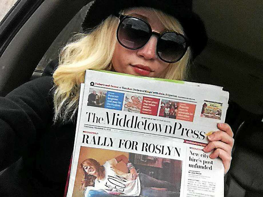 Roslyn Helmedach poses alongside a front-page story about her that appeared in a December edition of The Middletown Press. Photo: Courtesy Lori Helmedach