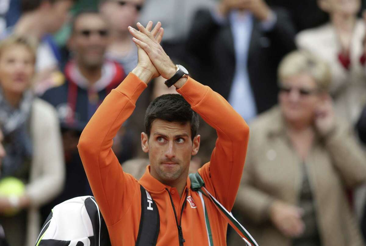 Novak Djokovic applauds after defeating Gilles Muller during their second-round match at the French Open Thursday in Paris.