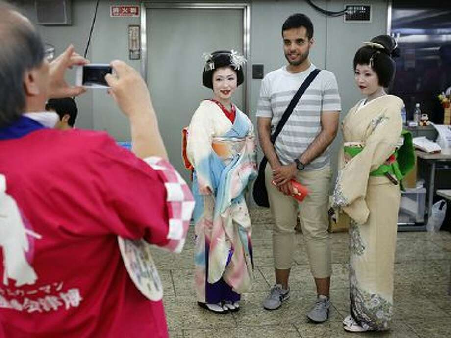 A foreign tourist poses with Japanese dancers dressed in kimonos during an exhibition to promote tourism and local products made and grown in Fukushima prefecture, where the tsunami-crippled Fukushima Dai-ichi nuclear power plant is located, in Tokyo, Thursday, Sept. 12, 2013. Photo: AP / AP2013