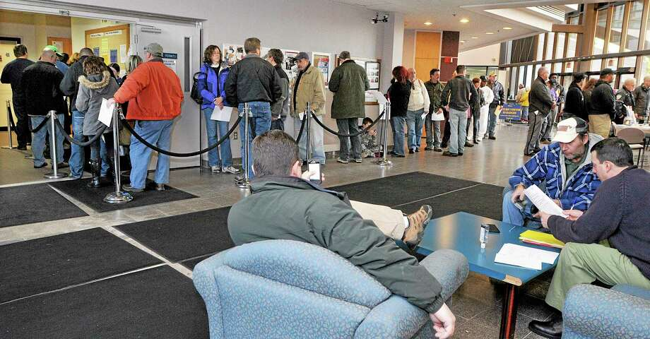 In this Dec. 27, 2013 photo, gun owners wait in line at the State of Connecticut Department of Public Safety office in Middletown, Conn., to renew hand gun permits, and register firearms classified as assault weapons prior to the Jan. 1 deadline.  The new regulations were enacted in April in response to the Sandy Hook Elementary School shooting. (AP Photo/The Middletown Press, Catherine Avalone) Photo: AP / The Middletown Press