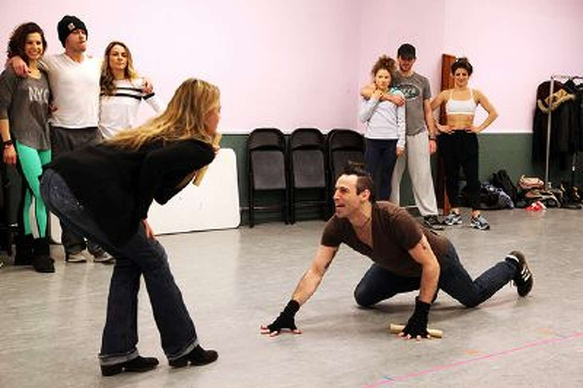 """In this Tuesday, Jan. 28, 2014 photo, Kate Rockwell, left, and Joey Calveri rehearse a scene from """"Rock of Ages"""" at a dance studio in New York. The cast of the Broadway show will be part of the televised pregame entertainment from outside MetLife Stadium in New Jersey for Sunday's Super Bowl."""