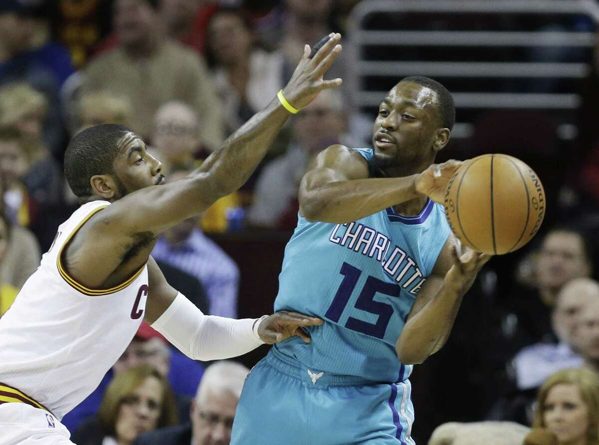 The Cavaliers' Kyrie Irving pressures the Charlotte Hornets' Kemba Walker, right, during Friday's game in Cleveland.
