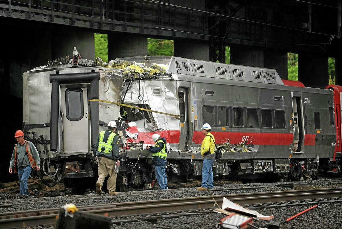 Metro-North employees work at the site of Friday's train derailment in Bridgeport. Conn. on Sunday, May 19, 2013. Crews will spend days rebuilding 2,000 feet of track, overhead wires and signals following the collision between two trains Friday evening that injured 72 people, Metro-North President Howard Permut said Sunday.