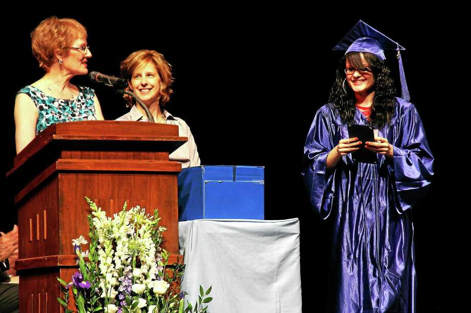 Kathleen Schassler — The Middletown Press In her address to fellow students, speaker Lizette DeJesus, 18, right, encouraged the class of 2015 to clear any hurdles they may face ahead in life during adult education's 70th annual graduation at the Middletown High School Performing Arts Center on La Rosa Drive. At the podium, from left, are Beverly Veronick, adult education teacher, and Stacie Dills, branch manager of Liberty Bank. Photo: Journal Register Co. / Kathleen Schassler All Rights