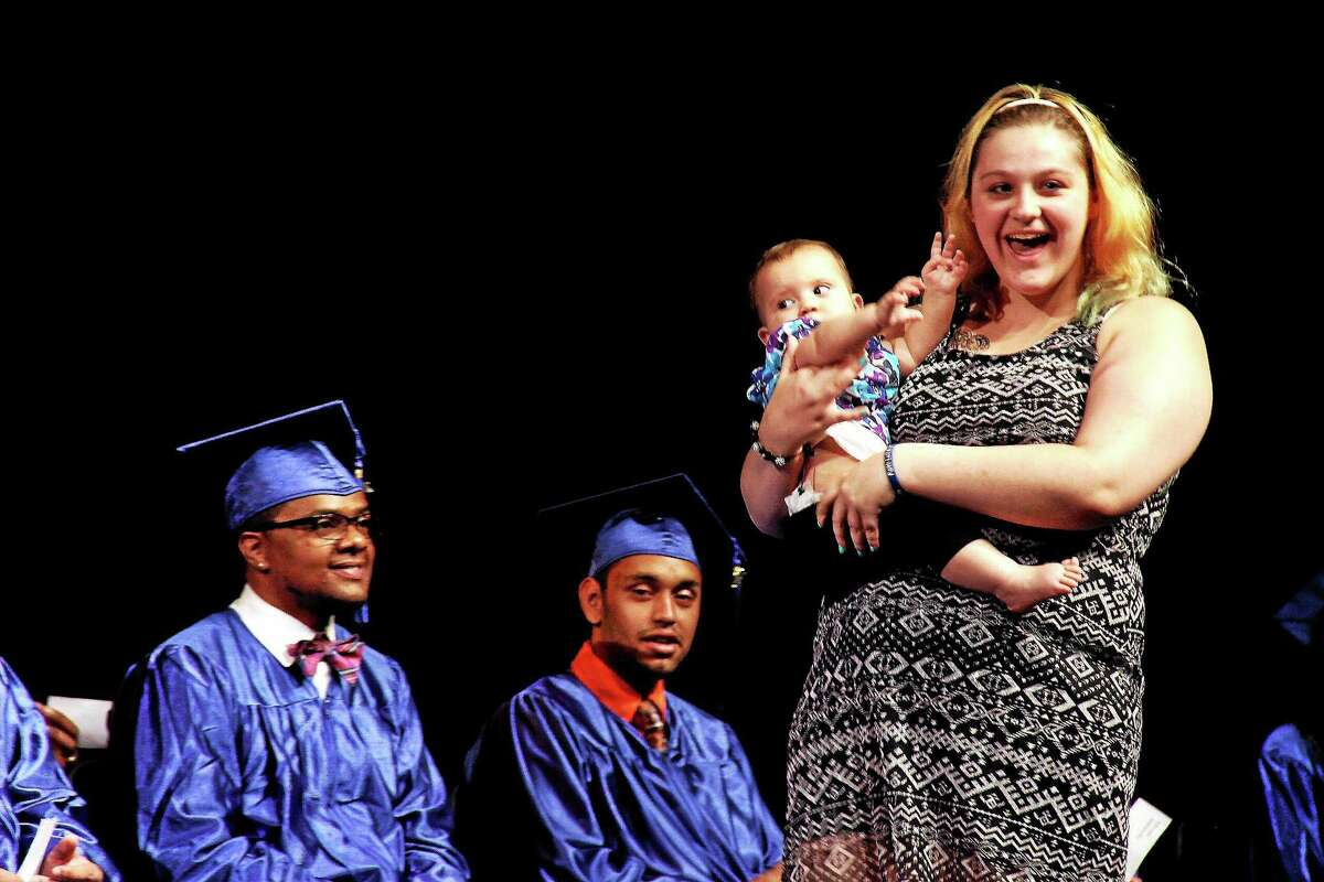 In all, 19 Middletown Adult Education Even Start Learning Program students — of all ages — earned their degrees this week at graduation exercises. Here, Amarissa Lesick steps on stage with baby Lillie Rivera.