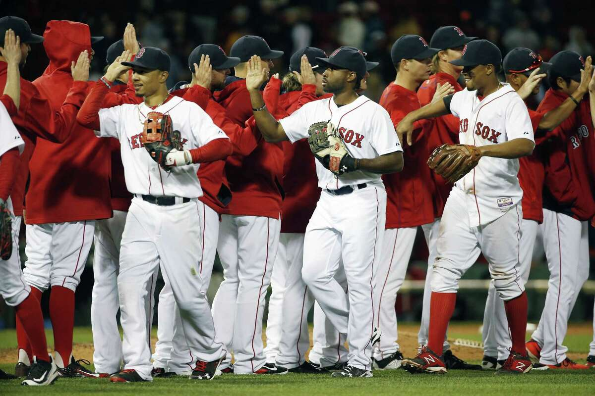 The Boston Red Sox, including, foreground from left, Mookie Betts, Jackie Bradley Jr. and Xander Bogaerts celebrate after defeating the Baltimore Orioles 8-0 in a baseball game in Boston, Saturday, Sept. 26, 2015. (AP Photo/Michael Dwyer)