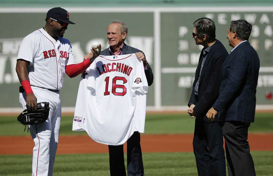 David Ortiz, left, presents Red Sox president and CEO Larry Lucchino, second from left, with a jersey and a ball as team owner John Henry, second from right, and chairman Tom Werner watch during a tribute before the Sunday's game. Photo: Michael Dwyer — The Associated Press  / AP